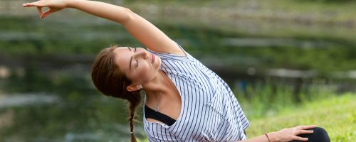 Young beautiful woman doing yoga exercise in green park near the pond. Exercices for improve the flexibility. Wellbeing and wellness. Healthy lifestyle and fitness concept.